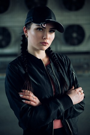 people, beauty, fashion, lifestyle concept -Young sexy woman with braids dressed in a black pants and a black bomber jacket, leather cap. Fashion girl at the industrial zone. Outdoors lifestyle portrait Stock Photo - 75818680