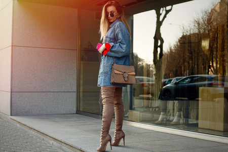 People, beauty, fashion, lifestyle and color concept - Detail of a beautiful young woman with a knee. Street style portrait of a stylish girl with long straight brown hear hear hessian boots.