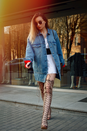 People, beauty, fashion, lifestyle and color concept - beautiful young woman with a knee. Street style portrait of a stylish girl with long straight brown hear hear hessian boots. Stock Photo