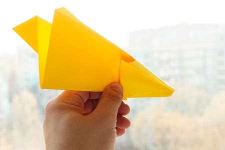 aerodynamic: holidays, tradition, style and minimalism concept - Yellow origami plane on a white background.