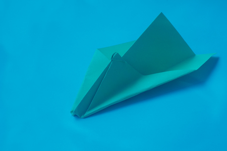 aerodynamic: holidays, tradition, style and minimalism concept - Yellow origami plane on a blue background.