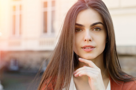 people, emotions, natural, beauty and lifestyle concept - Young beautiful stylish woman walking in brown coat, smiling, happy, street style, spring summer trend, blue jeans, white shirt, flirty. Closeup portrait of a happy young woman smiling, summer stre