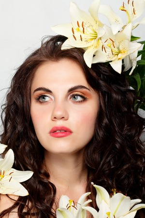 people, emotions, natural, beauty, flowers and lifestyle concept - Beauty girl takes beautiful flowers in her hands. Blowing flower. Hairstyle with flowers. Summer fairy portrait. Long permed hair.