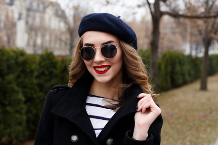 emotions, people, beauty and lifestyle concept - Girl Frenchwoman. Street photo of young woman wearing stylish classic clothes. Female fashion concept. French style. close-up portrait Stock Photo