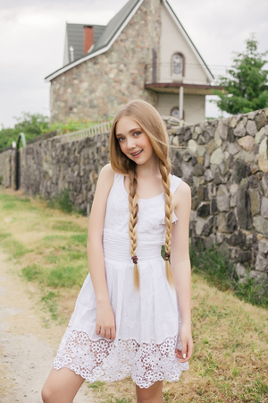 nature, architecture, people, fashion, natural concept -Fashion portrait of beautiful boho style girl near scandinavian house, house made of granite, straw. Girl in the country.