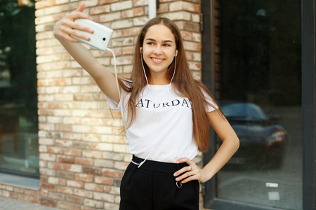 technologies,emotions, people, beauty, fashion and lifestyle concept - Carefree and happy, sunny spring mood. Charming young lady is making selfie on a camera. while on a walk in town outdoors