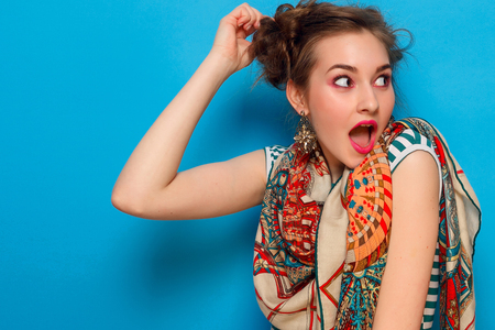 emotions, people, beauty, fashion and lifestyle concept - The portrait of young woman with shocked facial expression, over blue background