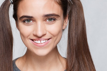 teeth,emotions, health, people, dentist and lifestyle concept - Healthy, beautiful smile The young woman's portrait with happy emotions, smile , Closeup of beautiful brunette woman with pretty eyes and gap between teeth