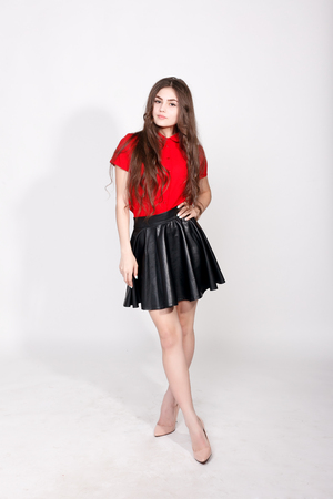 teeth,emotions, health, people and lifestyle concept - Fashionable young brunette woman posing wearing leather skirt and red shirt, looking at camera.