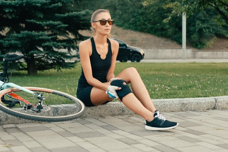 people, Sport,  health and lifestyle concept - Fit girl touching her injured knee after a bike accident day. Girl protecting knee for bicycle downhill in slow motion. girl has a pain in her knee