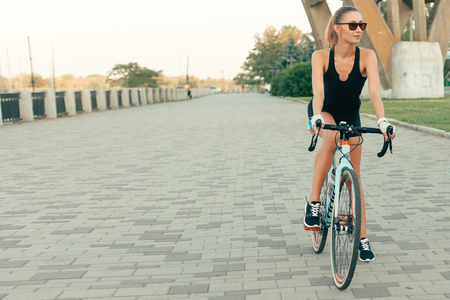 people, Sport, 4K , emotions, natural and lifestyle concept - Portrait of Pretty cute girl smiling beside her bike in the park with palms on a sunny day.