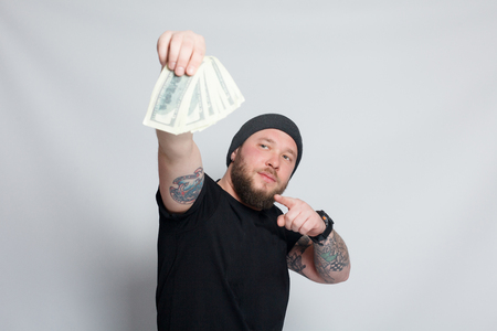 finance, people, lifestyle concept - bearded man. Funny guy is a lucky winner, she is holding a pile of money, he is surprised and can't believe it, he is happy to win one million dollar jackpot
