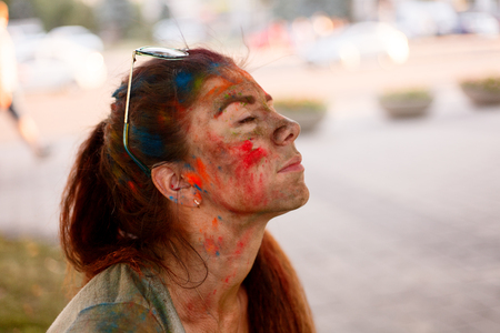 emotions, people, beauty, fashion and lifestyle concept - Portrait of a beautiful girl full of colored powder all over the body Banco de Imagens