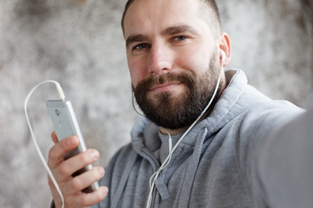 art, people, emotions, music,  and lifestyle concept - Model released man in studio puts ear phones rocks, electronic out to music. Young handsome bearded man listens music smartphone in earphones Stock Photo
