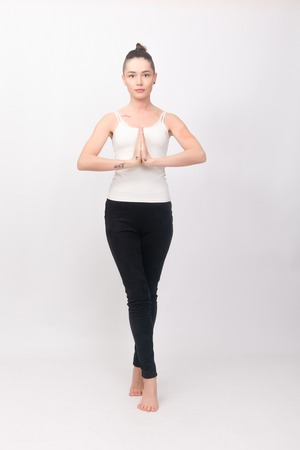 fitness, sport, training and lifestyle concept - Young woman doing yoga exercise. Portrait of young beautiful girl in white sportswear doing yoga practice.Woman doing stretching exercise Stock Photo