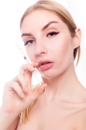 beauty, make up and people concept - Attractive young woman gets cosmetic injection, isolated over white background. Doctors hands making an injection in face. Beauty Treatment.