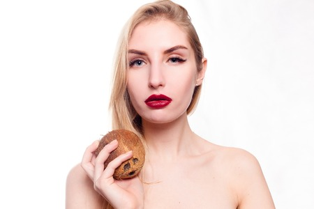 health, people, food and beauty concept - Beautiful young girl with a light natural make-up and perfect skin with coconut in her hand. Beauty face. Picture taken in the studio on a white background.