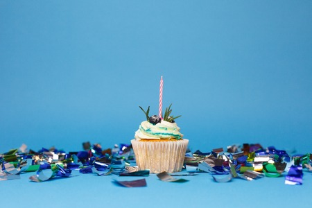 holiday, celebration, greeting and party concept - birthday cupcake with one burning candles over blue background, confetti. Confetti for a party.