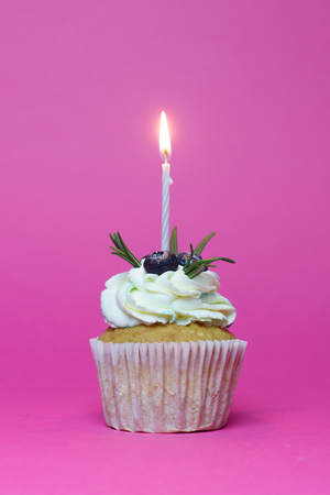 holiday, celebration, greeting and party concept - birthday cupcake with one burning candles over pink background Stock Photo