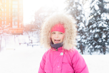 childhood, fashion, season and people concept - 4K Little Girl Playing in Snow Winter, View Happy Child Making Snowball, Snowman Par, Kids in Christmas Vacation. face of happy girl in winter clothes