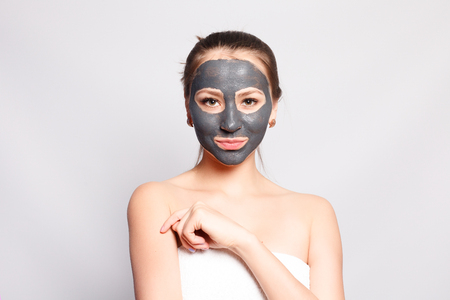 Woman Face Mask. Portrait Of Beautiful Girl Removing Cosmetic Black Peeling Mask From Facial Skin. Closeup Of Attractive Young Woman With Natural Makeup And Cosmetic Peel Mask On Face. High Resolution Stock Photo