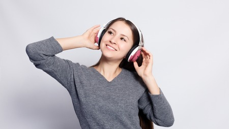 People, leisure and technology concept - happy woman or teenage girl in headphones listening to music from smartphone and dancing