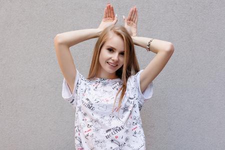 Jeune belle étudiante caucasienne heureuse avec de longs cheveux bruns en pull et jeans faisant des oreilles de lapin avec les mains, regardant à huis clos avec une expression de visage ludique et excité