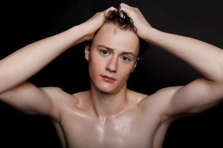 people, skincare and beauty concept - Wet young man with black hair on a black background. Portrait male with shaved chest . Mens skin care. Ripped muscular handsome man on black background