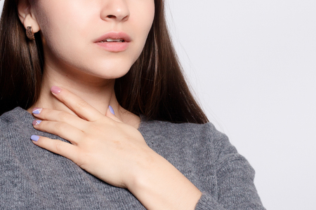 Illness, Health Care, people, Medicine concept - Throat Pain. Closeup Of Sick Woman With Sore Throat Feeling Bad, Suffering From Painful Swallowing. Beautiful Girl Touching Neck With Hand Stock Photo