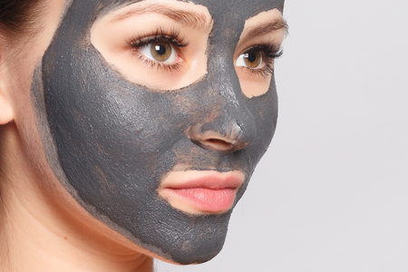 Woman Face Mask. Portrait Of Beautiful Girl Removing Cosmetic Black Peeling Mask From Facial Skin. Closeup Of Attractive Young Woman With Natural Makeup And Cosmetic Peel Mask On Face. High Resolution Foto de archivo