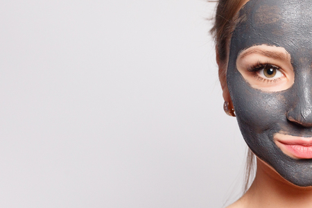 Woman Face Mask. Portrait Of Beautiful Girl Removing Cosmetic Black Peeling Mask From Facial Skin. Closeup Of Attractive Young Woman With Natural Makeup And Cosmetic Peel Mask On Face. High Resolution 免版税图像