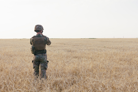 Soldier man standing against a field. Portrait of happy military soldier in boot camp. US Army soldier in the Mission. war and emotional concept. Imagens