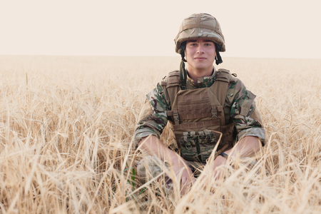 Soldier man standing against a field. Portrait of happy military soldier in boot camp. US Army soldier in the Mission. war and emotional concept. 免版税图像