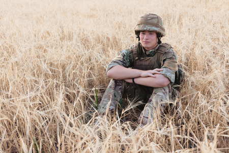 Soldier man standing against a field. Portrait of happy military soldier in boot camp. US Army soldier in the Mission. war and emotional concept. Banco de Imagens