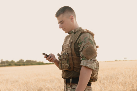 Mid section of military soldier using mobile phone in boot camp. letter from war. Reklamní fotografie