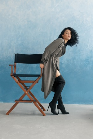 people, race, ethnicity and fashion concept - beauty black model posing in high boots. Young pretty beautiful mulatto woman sitting in director's chair at film. woman in gray raincoat, afro hairstyle