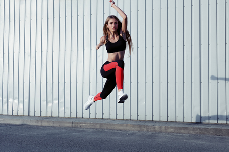Sportswoman jumping and stretching. Full length of healthy female exercising and jumping outdoors. Stock Photo