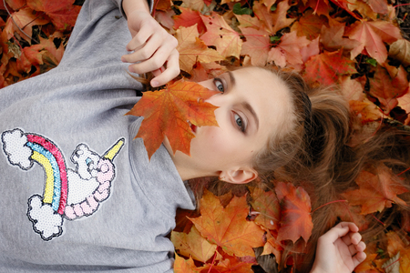 beauty, people, season and health concept - pretty little girl is lying in yellow Autumn leaves