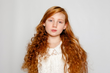 Fun Portrait of an Adorable Red Haired Girl on a Grey Background. Beauty, kid fashion, cosmetics, healthy hair. Hairdresser, makeup, shampoo. Stock Photo