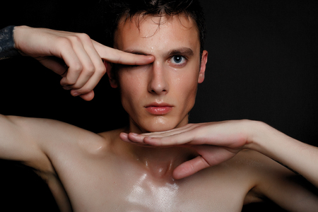 Handsome young man isolated. Beauty portrait of shirtless muscular man is standing on black background and looking at camera. Mens health.