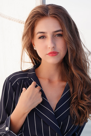 Attractive girl on a yacht at summer day. Close up of fashion portrait of stunning romantic woman posing yacht. Wearing an elegant dress, summer outfit. Blue sky. sunset Banque d'images - 109807858