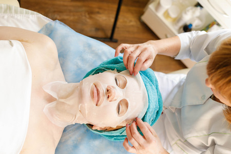 Collagen face mask . Facial skin treatment. Woman receiving cosmetic procedure in beauty salon. Bottle with moisturizing cream on background.
