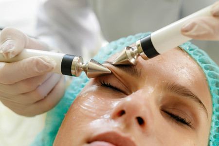 people, beauty, spa, cosmetology and technology concept - Cosmetologist makes the procedure microcurrent therapy of the facial skin of a beautiful, young woman in a beauty salon Banco de Imagens