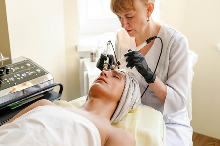 people, beauty, spa, cosmetology and technology concept - Cosmetologist makes the procedure microcurrent therapy of the facial skin of a beautiful, young man in a beauty salon Imagens