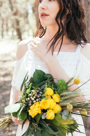Wedding walk in the pine forest. Sunny day. Wedding couple in the forest. Beautiful Bride and groom on a walk. White wedding dress. Bouquet of peonies and hydrangeas. Stock Photo