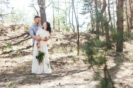 Wedding walk in the pine forest. Sunny day. Wedding couple in the forest. Beautiful Bride and groom on a walk. White wedding dress. Bouquet of peonies and hydrangeas. Stock fotó