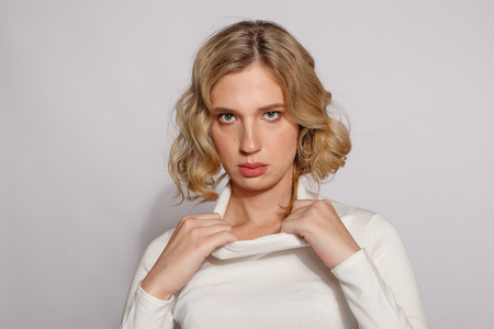 Portrait of beautiful transgender woman with blond hair over gray background