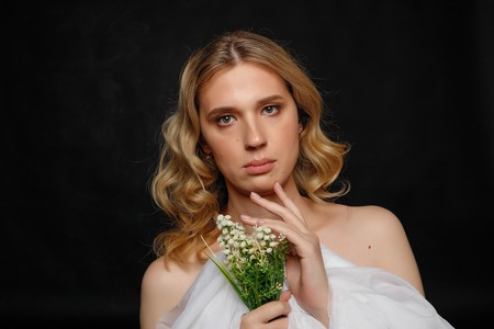 beautiful young transgender with blond hair, dark blue background, smiling, holding flowers and white cloth