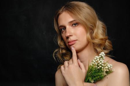 Hermosa joven con cabello rubio, fondo azul oscuro, sonriendo, sosteniendo flores y tela blanca