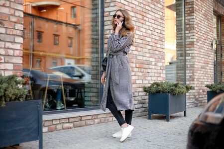 smiling elegant woman in trench coat walking and drinking coffee from paper cup . smiling woman with curly hair look at camera smile walking slow motion face sunset beautiful lady outdoor closeup cute 写真素材